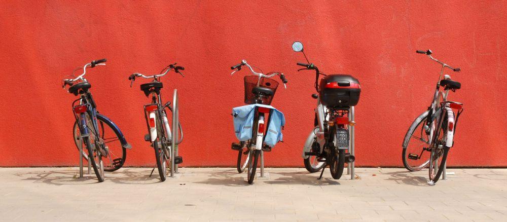 vier fietsen en een scooter voor een rode muur bij pagina over mobiliteitsscan
